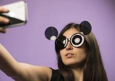 少妇在紫色背景做在黑老鼠太阳镜的Selfie 照片在最新的智能手机使用Google 库存图片