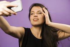 少妇在紫色背景做Selfie 女孩获得做照片的乐趣在最新的智能手机 库存照片