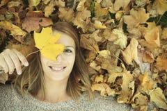少妇在美丽的秋天公园 图库摄影