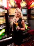 少妇在老虎机的赌博娱乐场 库存照片