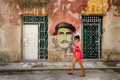 少妇在老Hava的一张切・格瓦拉画象前面走 库存图片