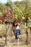少妇在葡萄园里在秋天在意大利小山 库存照片