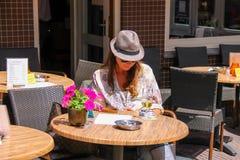 少妇在街道咖啡馆坐普遍的商店街道 图库摄影