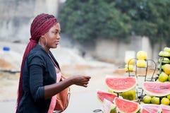 少妇在街道水果市场上 库存照片