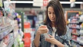 少妇在超级市场买化妆用品,她打开有液体的瓶并且嗅到它然后微笑和 股票录像
