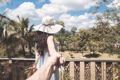 少妇在阳台或大阳台的背面图帽子的和礼服享受握男性手的热带森林风景 免版税库存照片