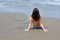 少妇在面对海洋的海边在ealy早晨 库存照片