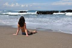 少妇在面对海洋的海边在ealy早晨 免版税库存图片