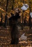 少妇在飞行乐谱用纸的无意识而不停地拨弄小提琴和秋天停放背景 免版税库存照片