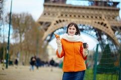 少妇在巴黎用咖啡和新月形面包 免版税库存照片