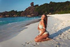 少妇坐一个美丽的热带海滩 免版税库存照片