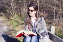 少妇坐一条长凳在有她的狗的秋天公园 免版税库存图片
