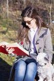 少妇坐一条长凳在有她的狗的秋天公园 免版税库存照片