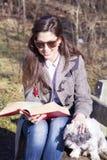少妇坐一条长凳在有她的狗的秋天公园 库存图片