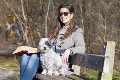 少妇坐一条长凳在有她的狗的秋天公园 免版税图库摄影
