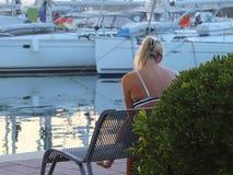 少妇坐一条长凳在沿海公园和观看的游艇在海湾小游艇船坞 库存照片
