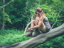 少妇坐下落的树在森林里 免版税库存照片