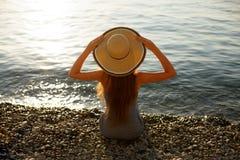 少妇坐与海滩礼服的小卵石岸在拿着在她的头的一个草帽 后面看法画象  免版税库存照片