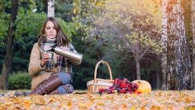 少妇坐倒从一个热水瓶的野餐热的茶在秋天公园 女孩在南瓜附近坐地毯 免版税图库摄影