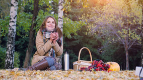 少妇坐喝从一个热水瓶的野餐热的茶在秋天公园 女孩在南瓜万圣夜附近的地毯 免版税图库摄影