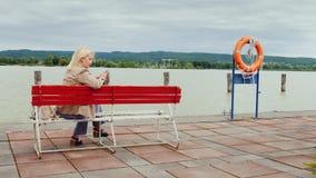 少妇坐在一个大湖的背景的一条长凳 使用一个手机 balaton匈牙利湖 股票视频