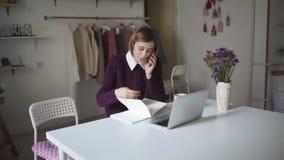 少妇坐在桌上和谈话由手机 使用妇女的膝上型计算机 股票录像