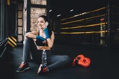 少妇坐地板在健身房的坚硬锻炼以后 库存图片