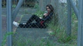 少妇坐地面和倾斜在篱芭滤网在空的街道 影视素材
