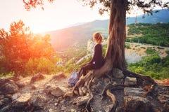 少妇坐山在日落 夏天横向 免版税库存照片