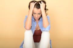 少妇坐握她的头发沮丧地的地板 免版税库存图片
