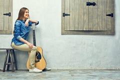 少妇坐有吉他的街道 免版税库存图片