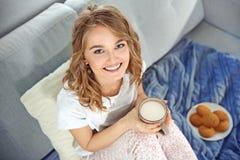 少妇坐有杯子的沙发牛奶和曲奇饼 免版税图库摄影