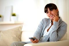 少妇坐有电视遥控的长沙发 图库摄影