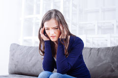 少妇坐有的沙发头疼偏头痛 免版税库存照片
