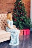 少妇坐沙发在与礼物盒的一棵圣诞树附近 圣诞节概念查出的新的空白年 免版税库存照片