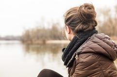 少妇坐湖边在早期的春天 免版税库存图片