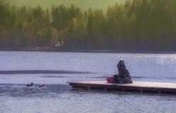 少妇坐湖Bleds码头 库存图片