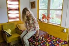 少妇坐的加有厚软垫的手提箱在床上 免版税库存照片