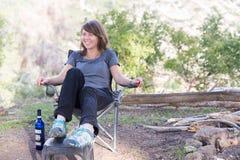 少妇坐的椅子在森林里 免版税图库摄影