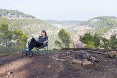 少妇坐的椅子在森林里 免版税库存照片