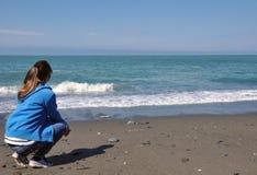 少妇坐看海的海滩 免版税库存照片