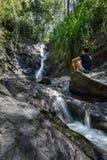 少妇坐看瀑布的岩石 免版税图库摄影