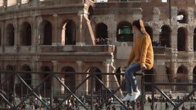 少妇坐看罗马罗马斗兽场的篱芭在意大利 女孩在罗马享受假期 慢的行动 股票视频