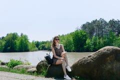 少妇坐石头由湖在俄罗斯 库存图片