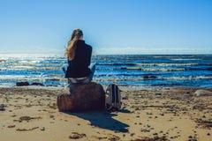 少妇坐石头在海边 库存照片