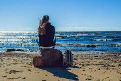 少妇坐石头在海边 库存图片