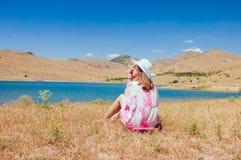 少妇坐草甸在湖附近 库存图片