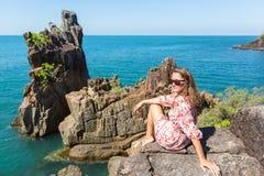 少妇坐酸值张沿海岩石  库存照片