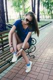 少妇坐长凳在公园,做她的鞋带 免版税图库摄影