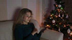 少妇坐长沙发,单独,在圣诞节 股票视频